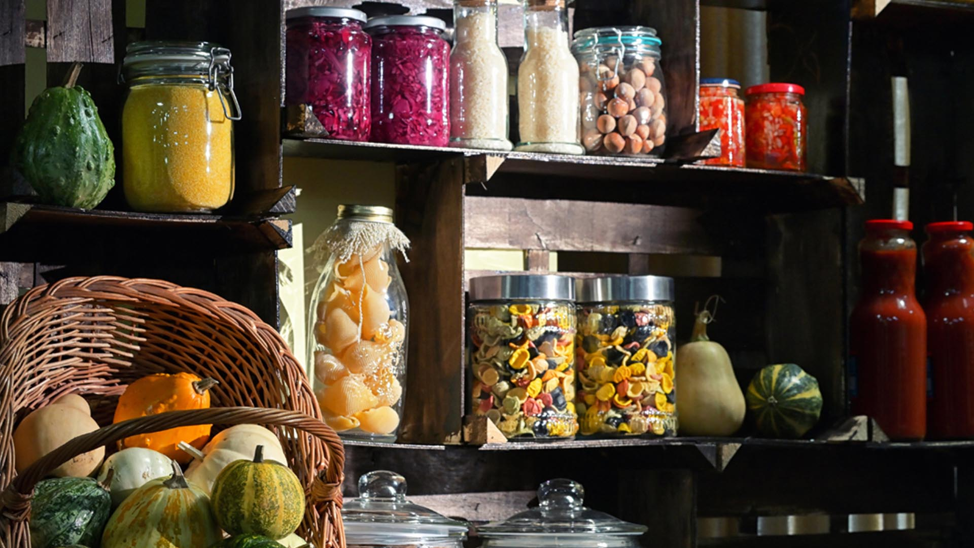 Dark wooden shelved pantry shelving full of glass jars of various local, fresh spices and dried and fresh foods including pasta, squash, beets, rice, candies and walnuts.
