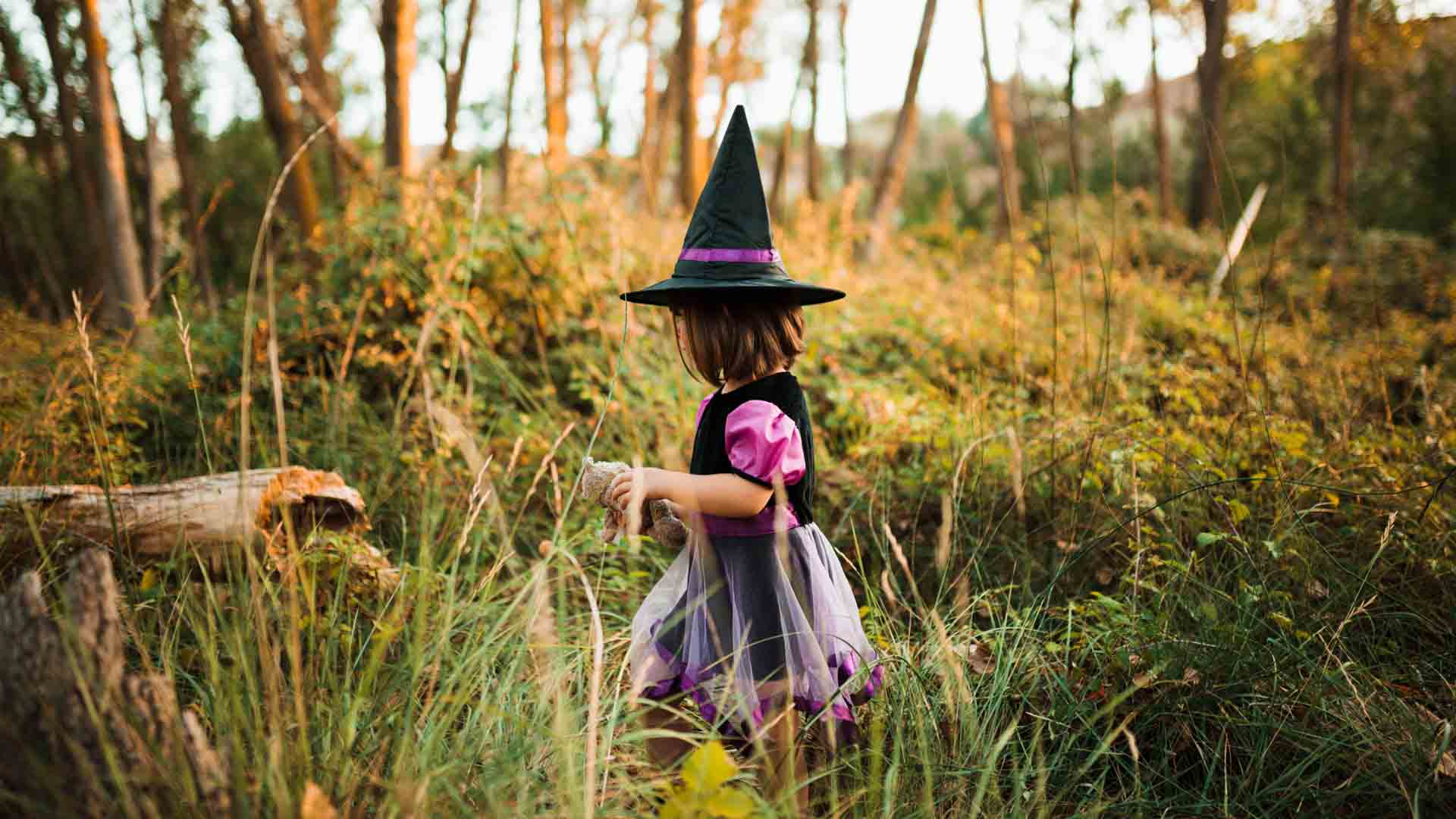 Little girl walking through a field wearing a witch hat.