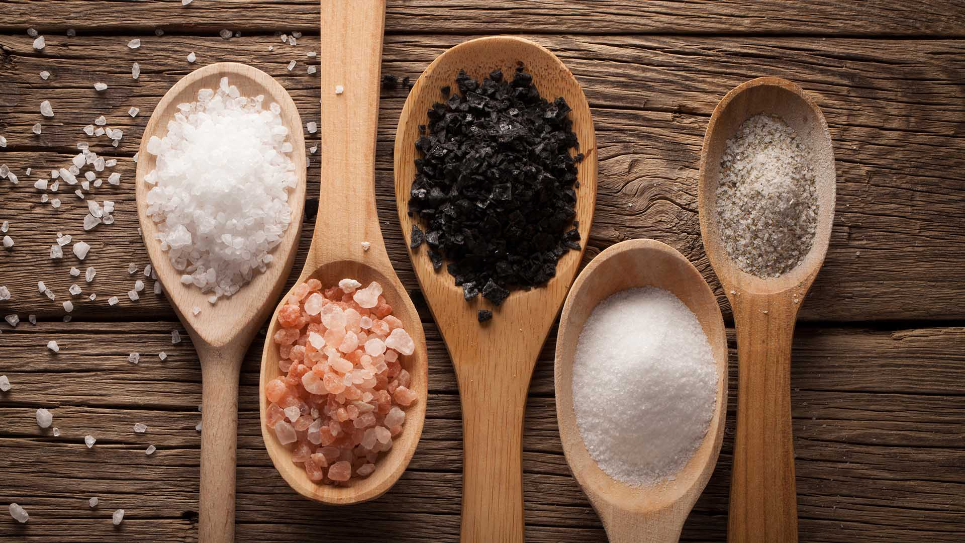 Wooden Spoons with different types of salt in each on wooden surface