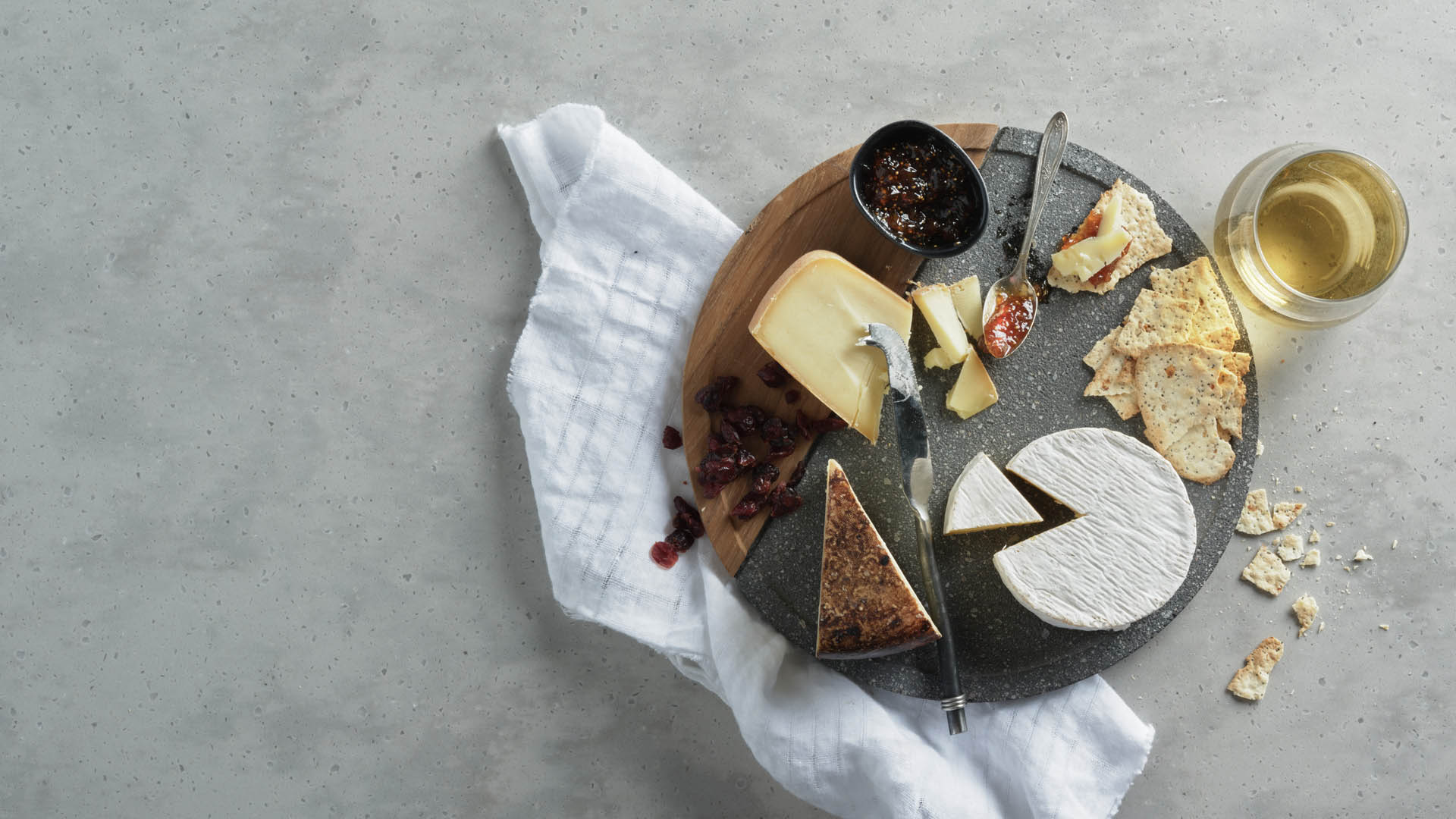 A round wooden board with three different cheeses, crackers, jams on a marble countertop with a glass of white wine on the side.