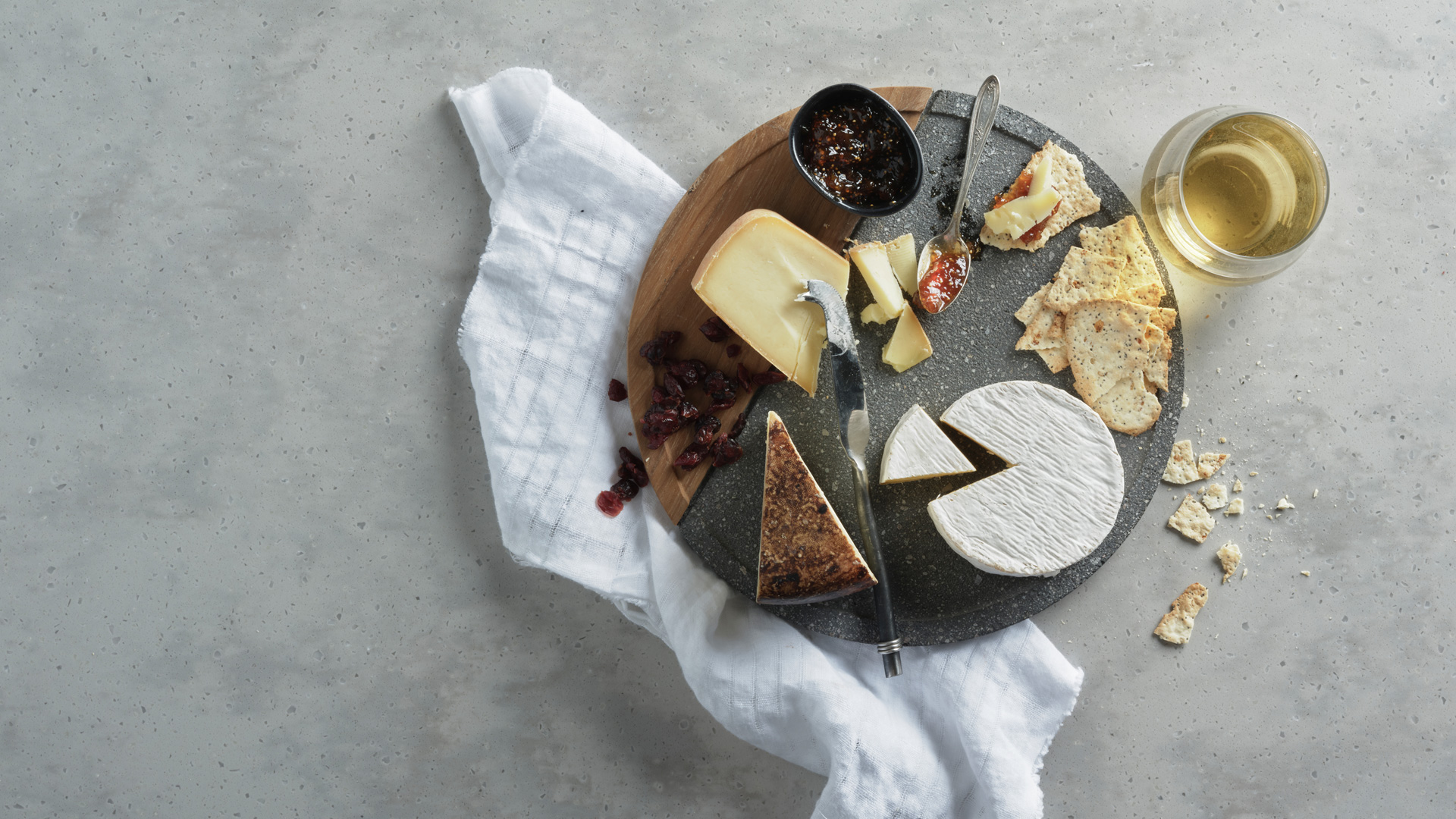 Selection of three cheeses and wine on a sphere grey marble board, with scattered cranberries, crackers, and jam spread in a small bowl with a white napkin on the left side.