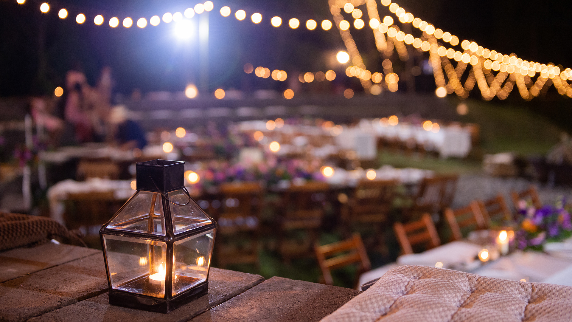 A lit lamp with a candle inside in an outdoor patio with tables and twinkle lights.