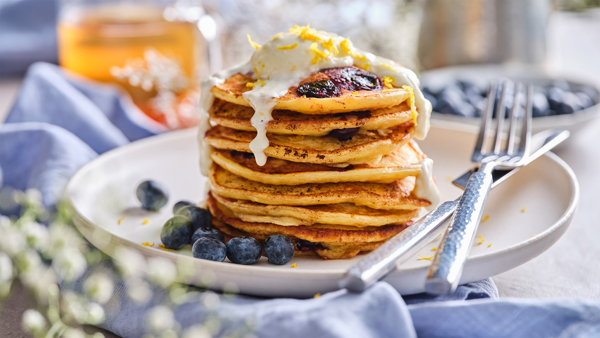 Ten Lemon and Blueberry Ricotta Pancakes are stacked on a stoneware plate, and topped with lemon cheesecake drizzle.