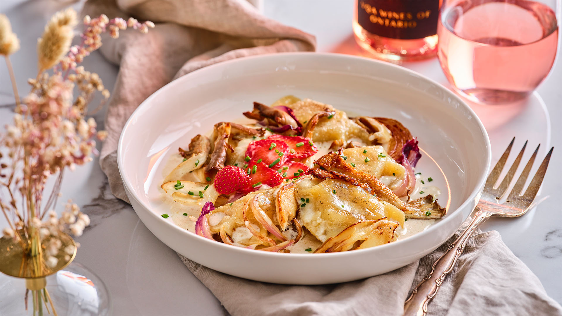 A white bowl is filled with duck pierogies with creamy Ontario parmesan sauce next to a glass filled with rose wine.