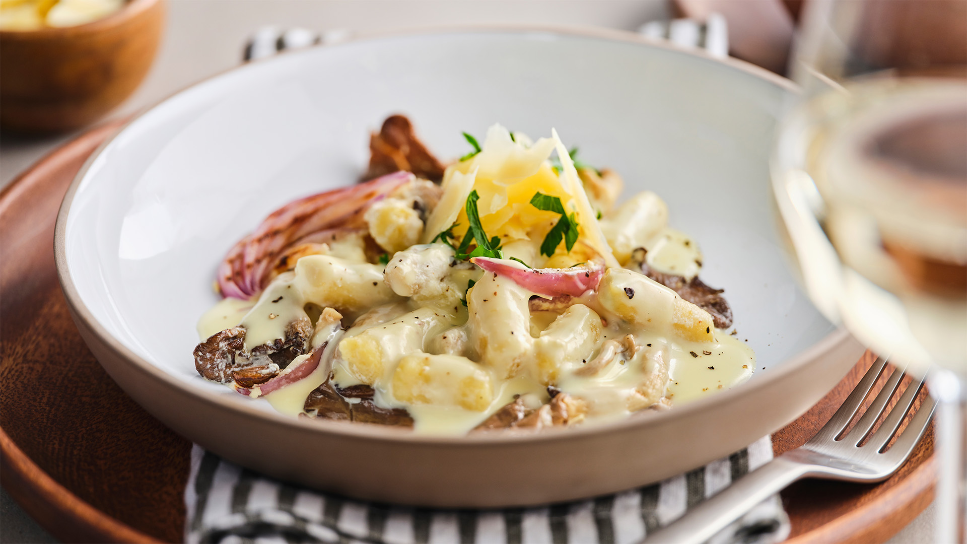 A white and beige earthenware bowl is filled with Parisienne Gnocchi with Ontario cheddar, fresh herbs, grilled mushroom and onion in a Chardonnay cream sauce.