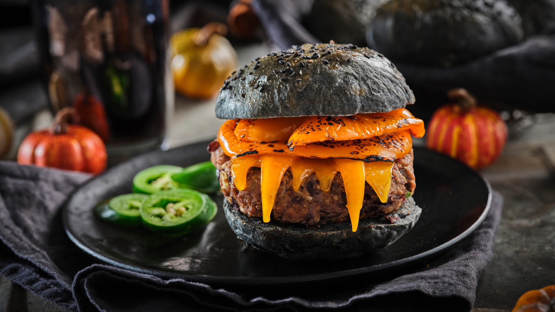 Burger with black buns, orange pepper, and melted cheddar cheese on a black plate beside a small collection of jalapeños.