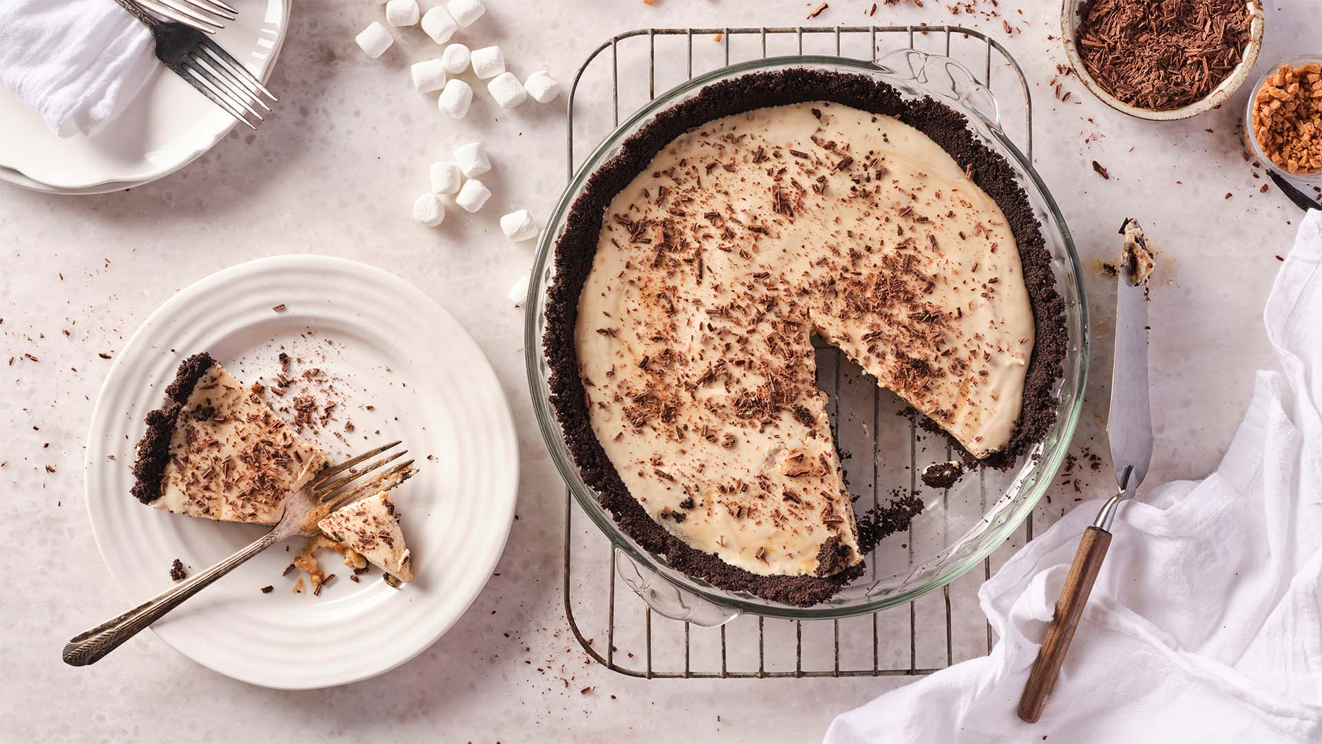 Overhead shot of Butter coffee toffee pillow pie in round baking dish set on top of a metal rack.