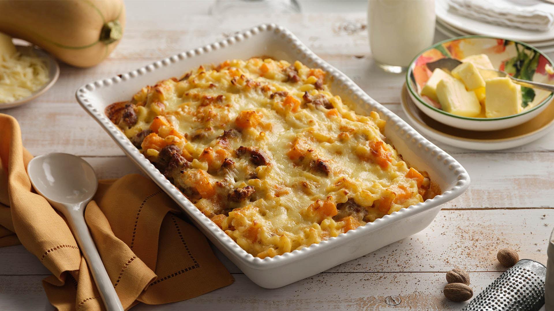 Side shot of white rectangular baking dish containing Butternut squash and sausage macaroni on wooden surface.