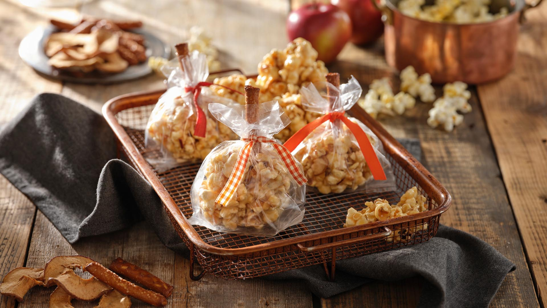 3 Caramel popcorn balls with pretzel stick handles wrapped in plastic tied with white and red checkered ribbons on a metal serving tray