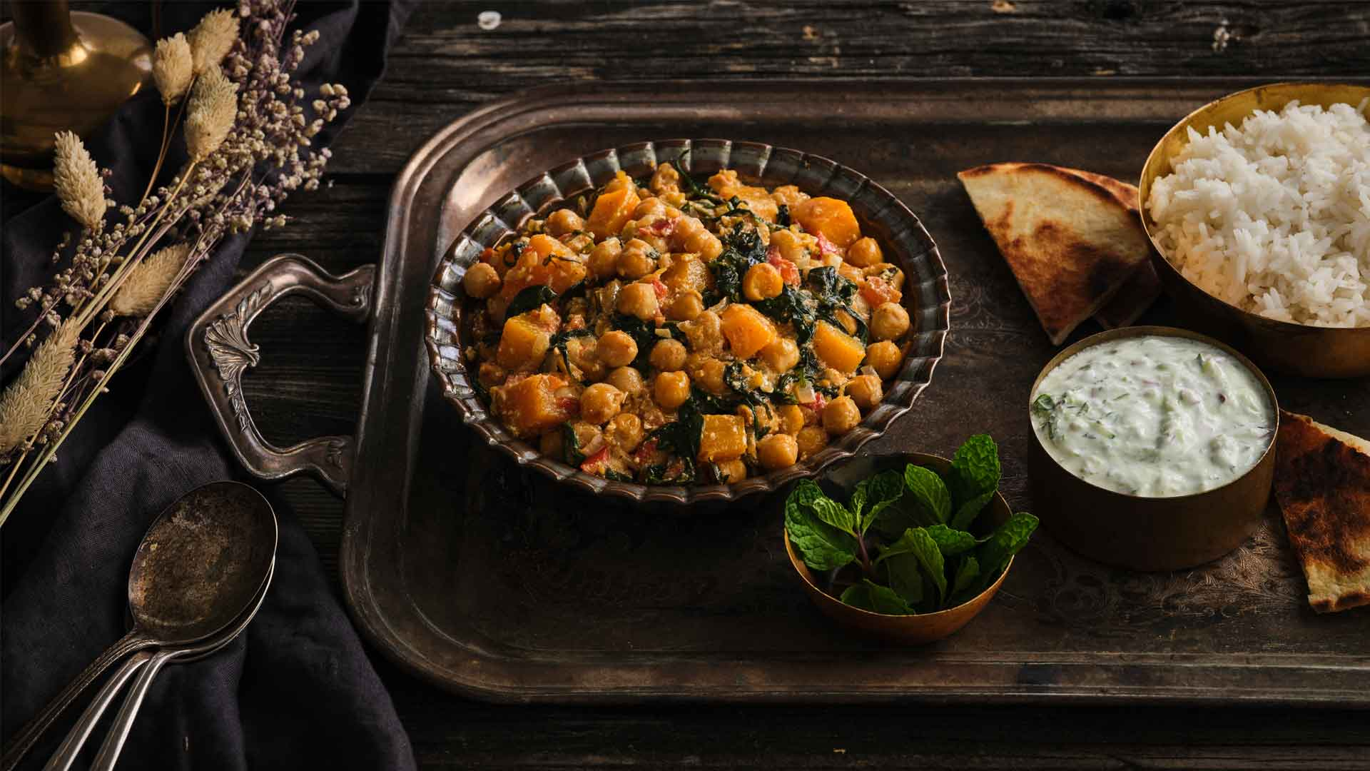 Side shot of chana masala in a bowl next to a bowl of dip, rice and pita on a brass serving tray.