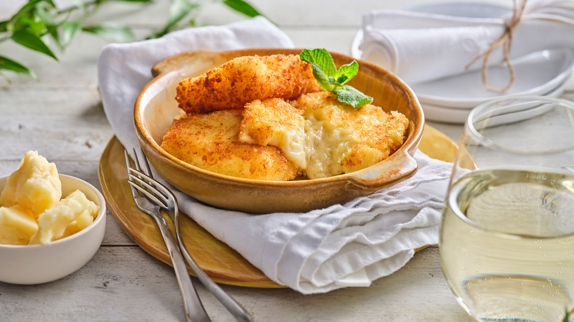 Side shot of Cheese Fondu in a round light brown pan on top of a white napkin.
