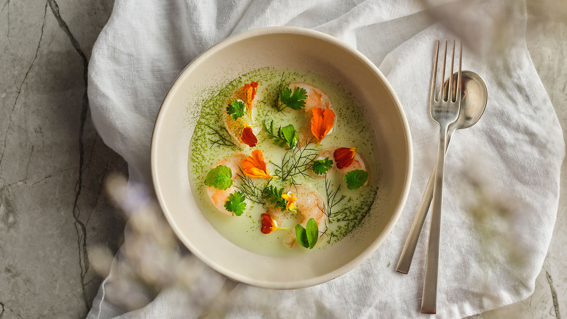 Overhead shot of chilled shrimp in a cream coloured round bowl next to utensils.