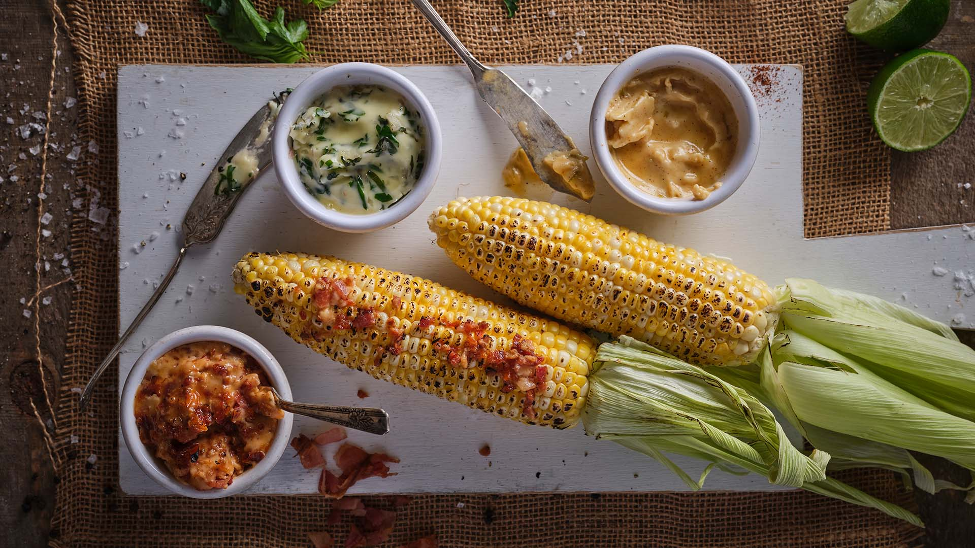 Overhead shot of two cobs of corn with flavoured compound butters slathered on them next to small prep bowls containing compound butters on a white serving board on top of a wooden surface.