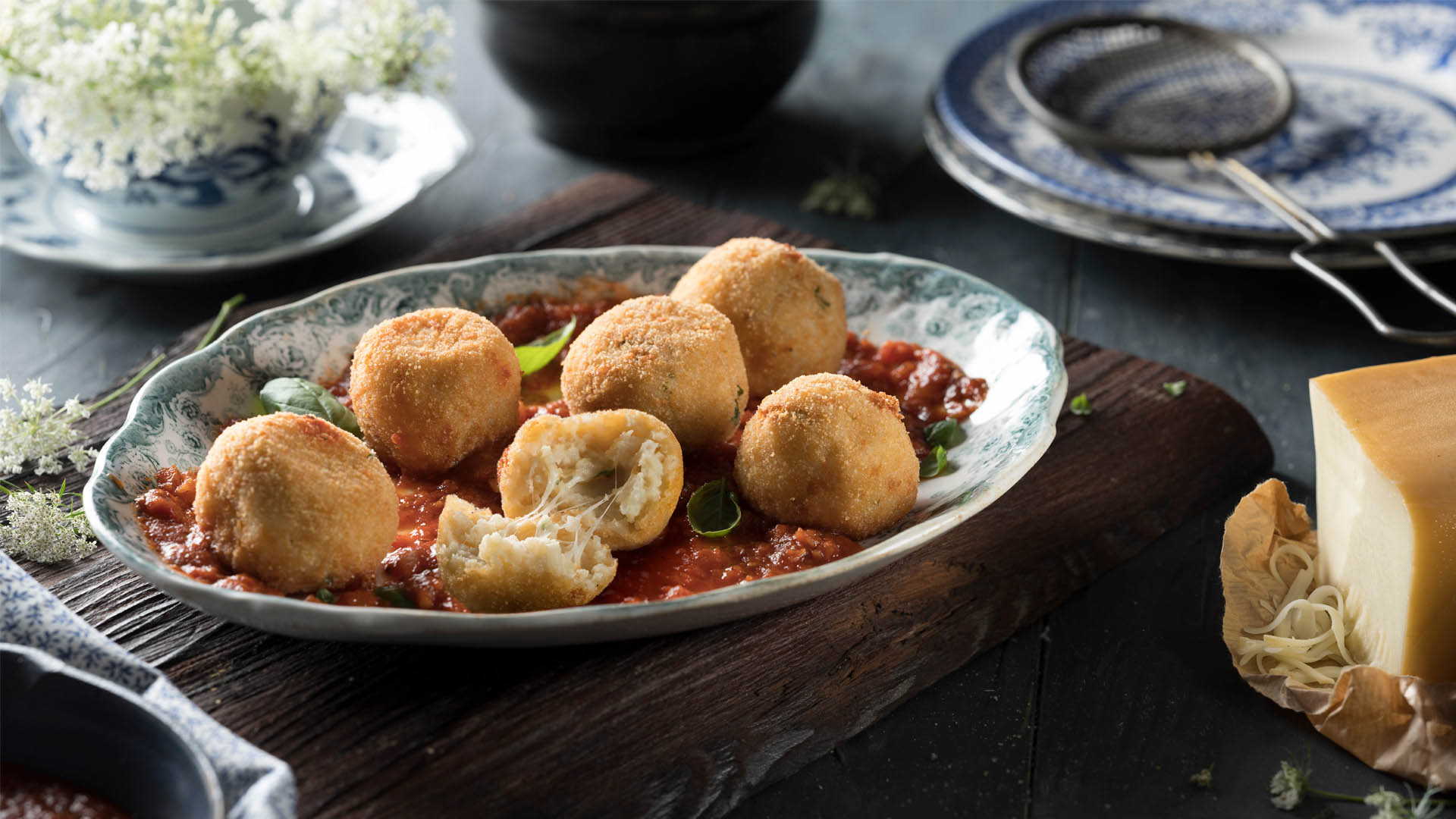 A dark grey bowl with ornate details, with golden  double cheese arancini balls in tomato sauce, all sitting on a dark wood table top, surrounded by flowers, a cast iron pan, and additional plates and serving of arancini balls.