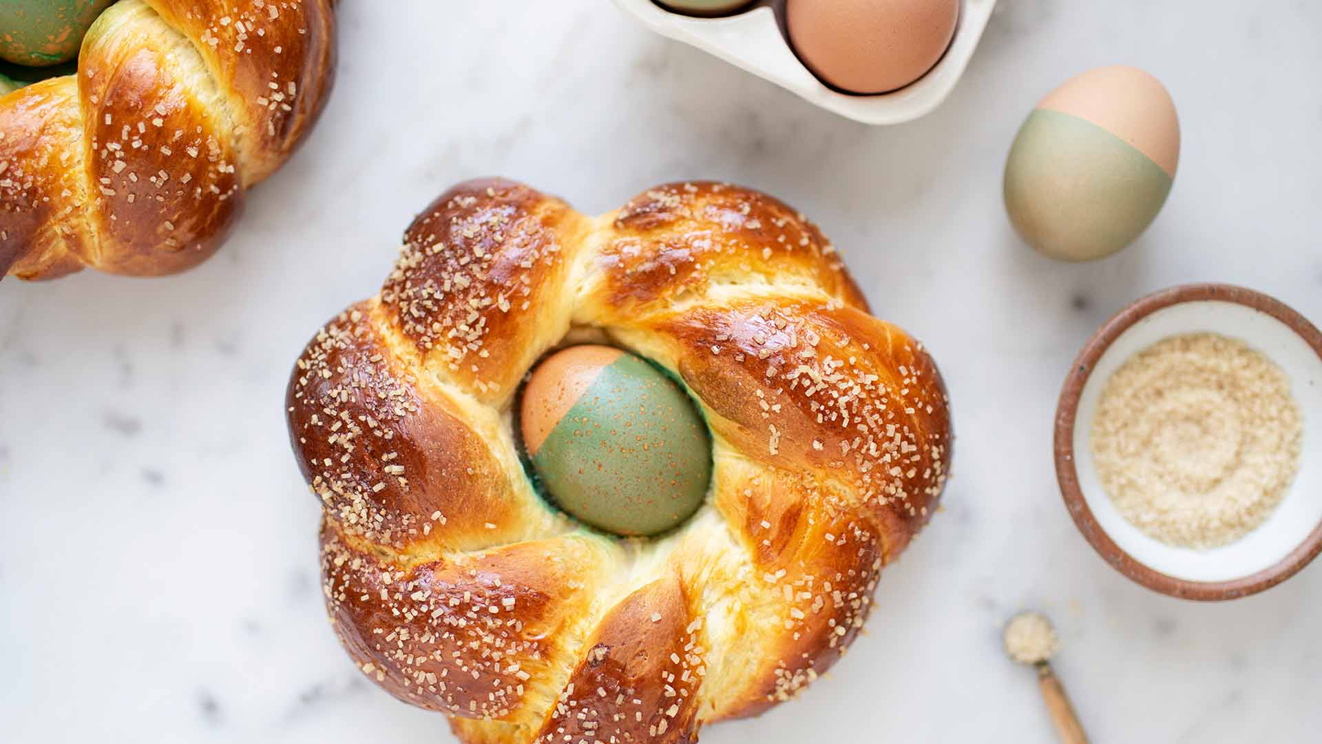 Overhead shot of easter bread on white surface with a green and light pink egg in center.