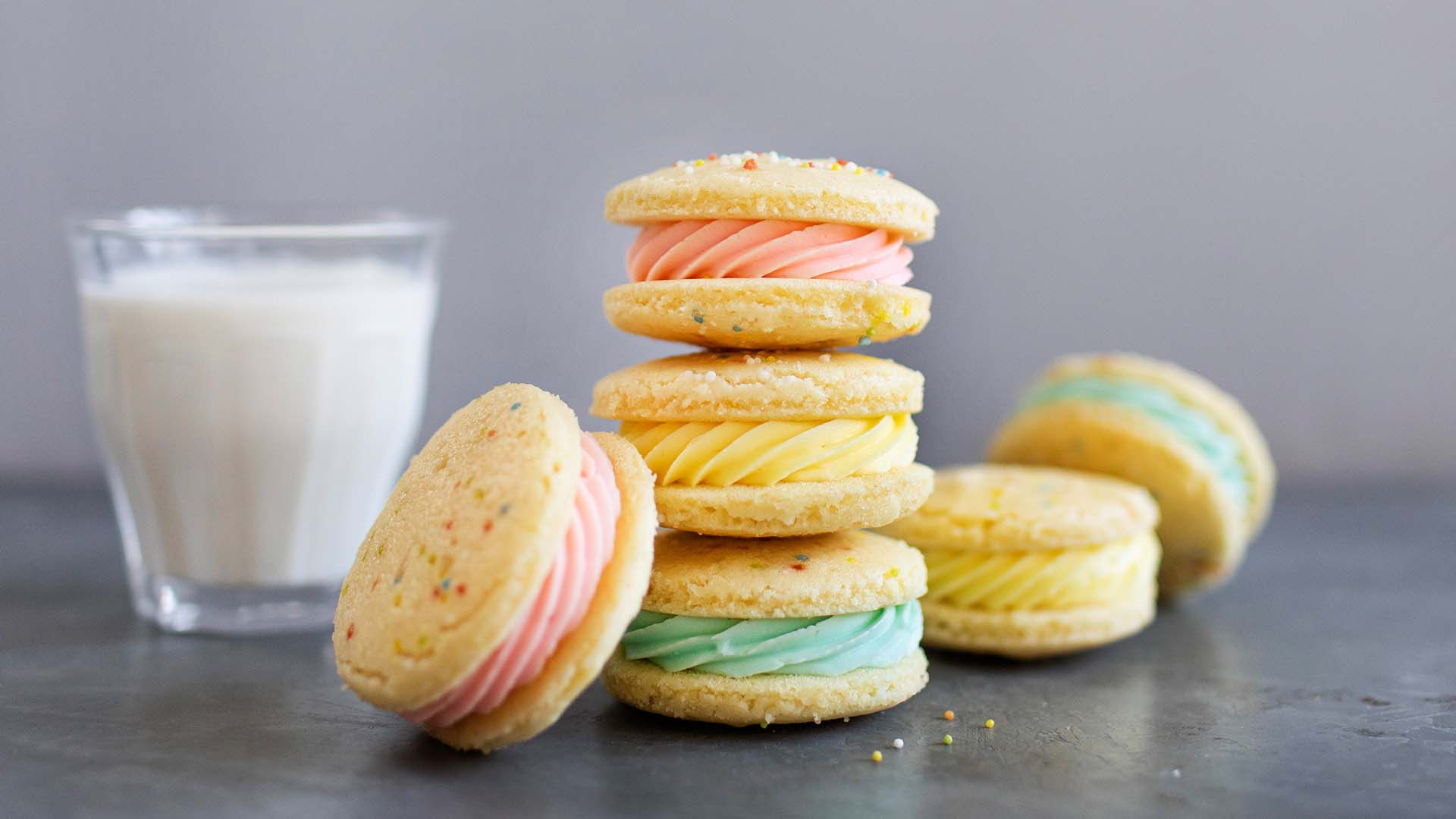 Side shot of stack of faux macarons with green and pink icing centre next to a small glass of milk.