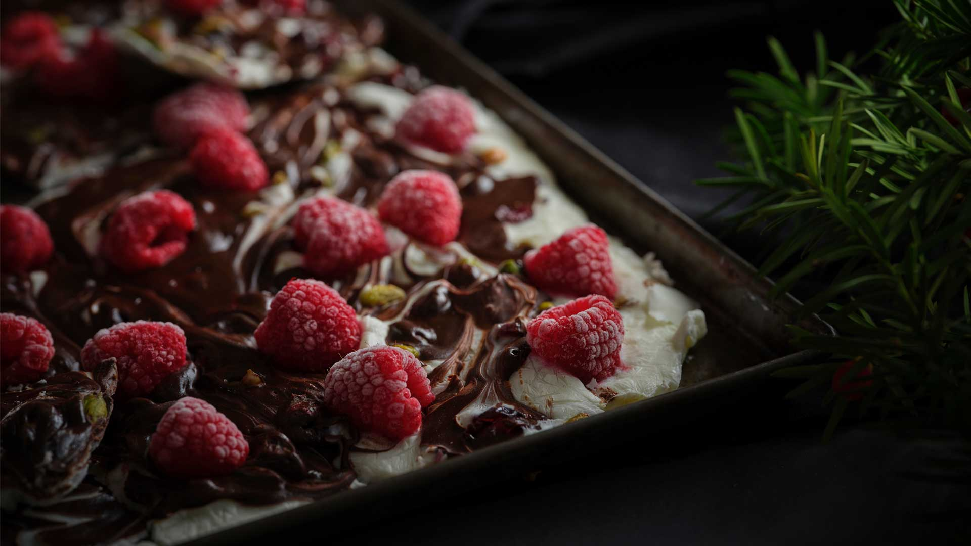 Yogurt chocolate berry, nuts and seed bark in a pan. Raspberries on top