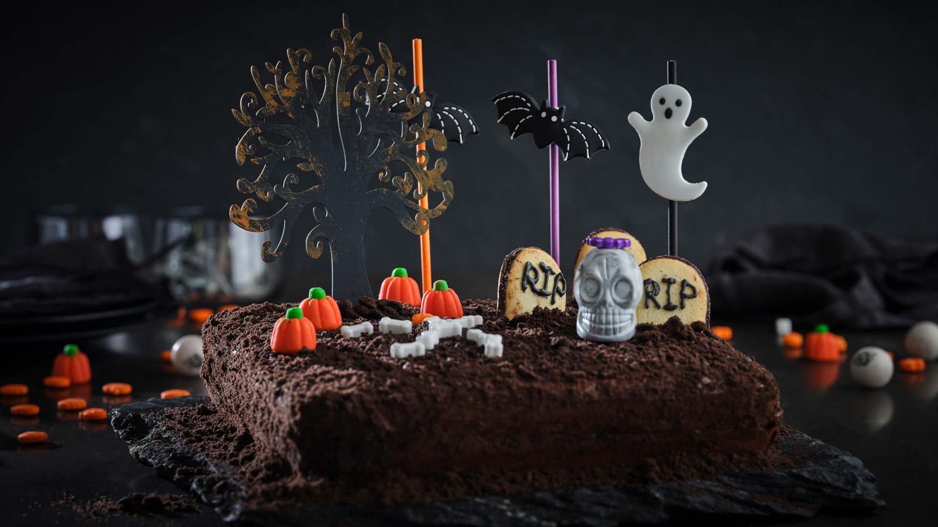 Brown Cake with black tree decoration, cookie tombstones, candy pumpkins, candy bones and bat and ghost decorations on a black surface.