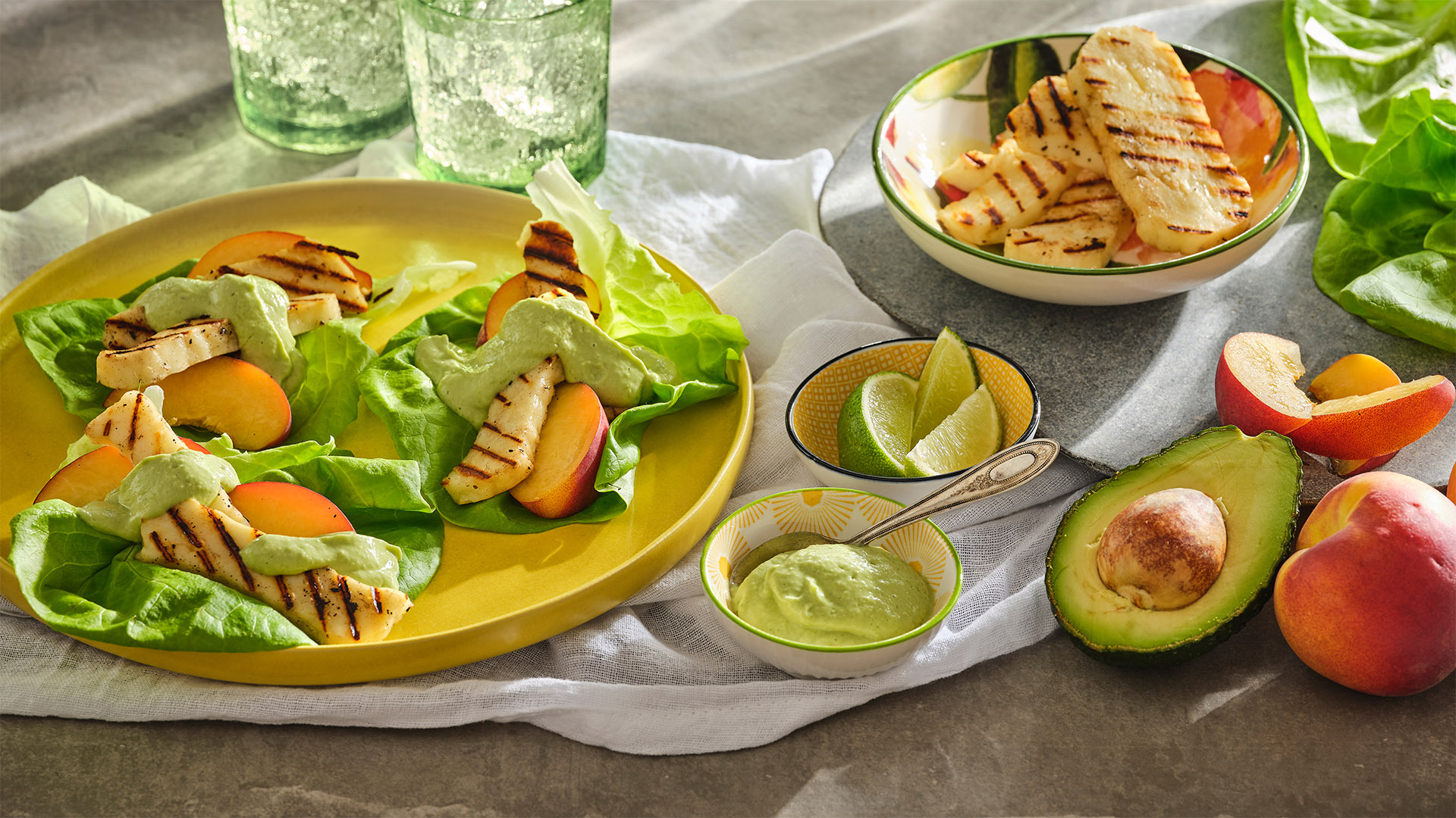 Green goddess lettuce leaf tacos on a yellow round plate next to an avocado half and a peach.