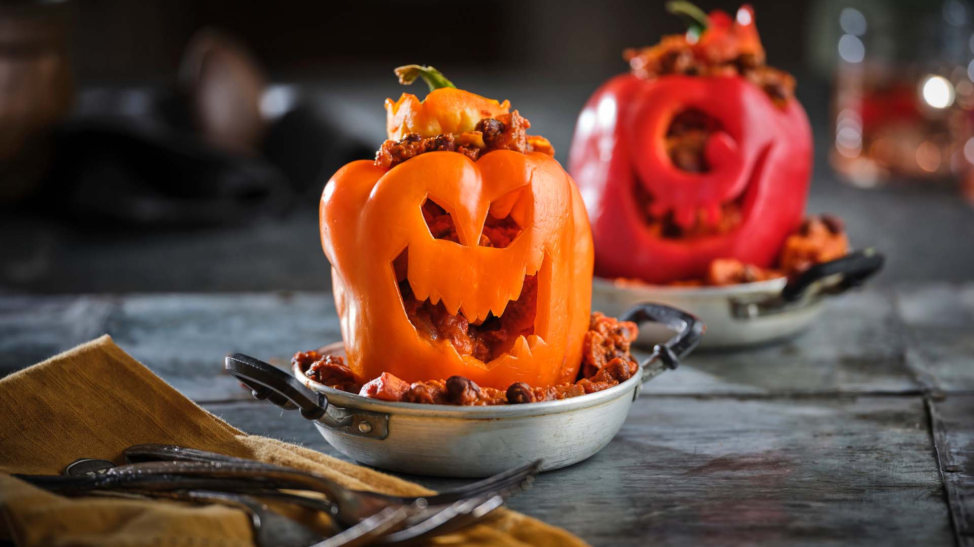 Red & Orange pepper with halloween face carving stuffed with chili