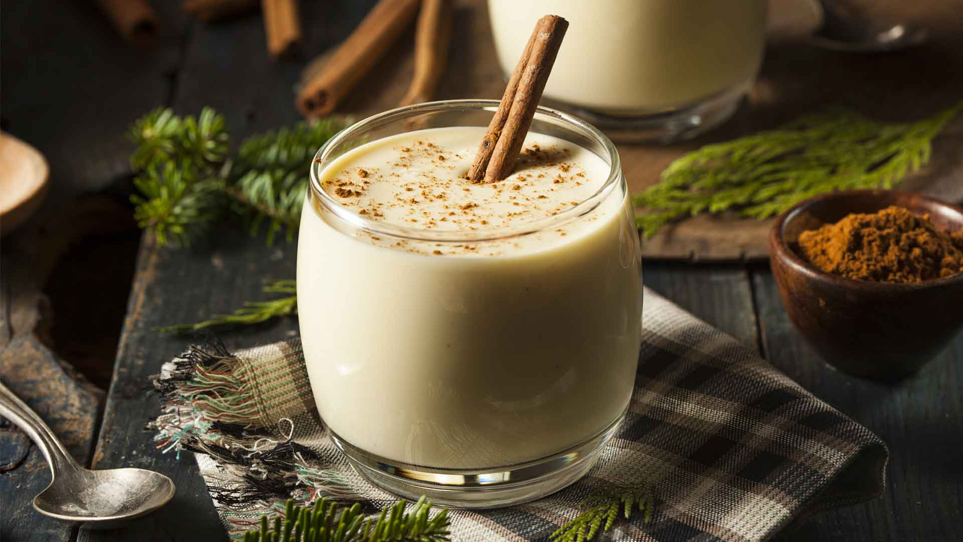 Side shot of eggnog in small glass with cinnamon stick