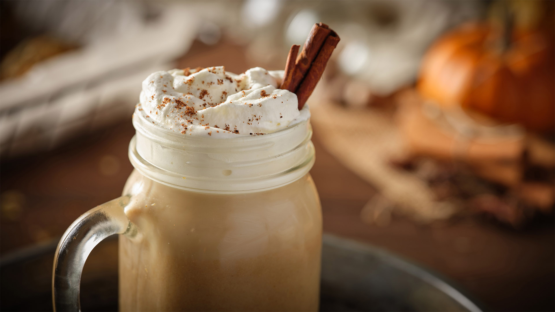 Pumpkin spice latte topped with whipped cream and a straw, inside a glass mason jar sitting on a blue plate. Faded background.