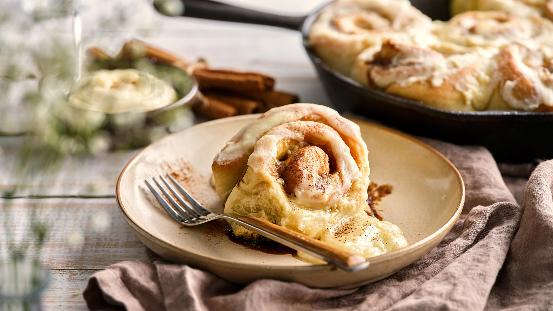 A cast iron pan is filled with Mascarpone Brioche Cinnamon Rolls and sits next to a plate with a serving.