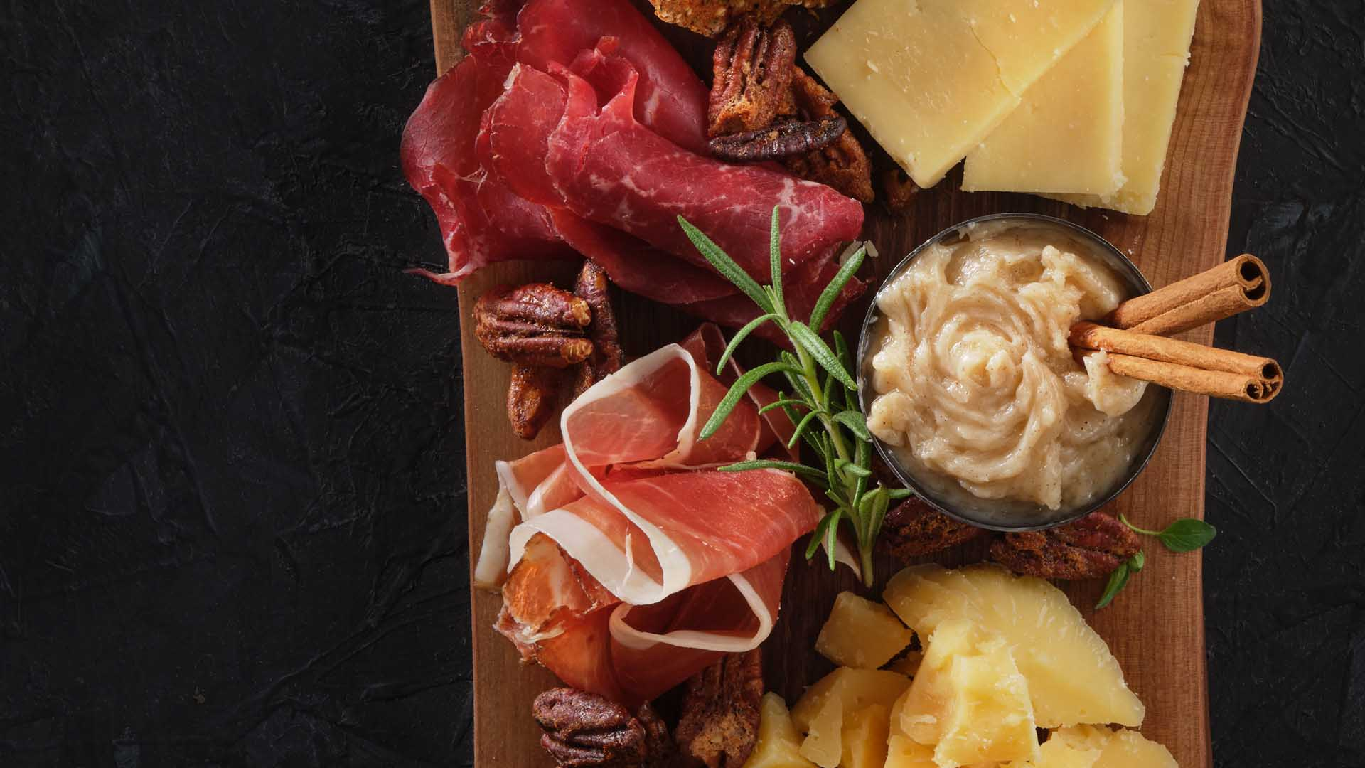 Overhead shot of harvest board featuring prosciutto, dips and other board elements.