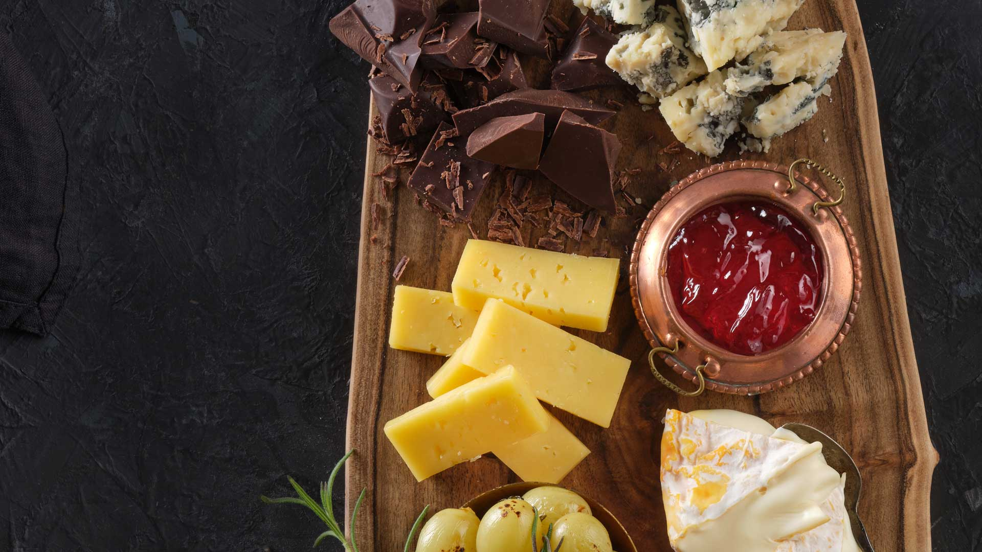 Overhead close up shot of board with grapes, two cheeses chocolate and dip.