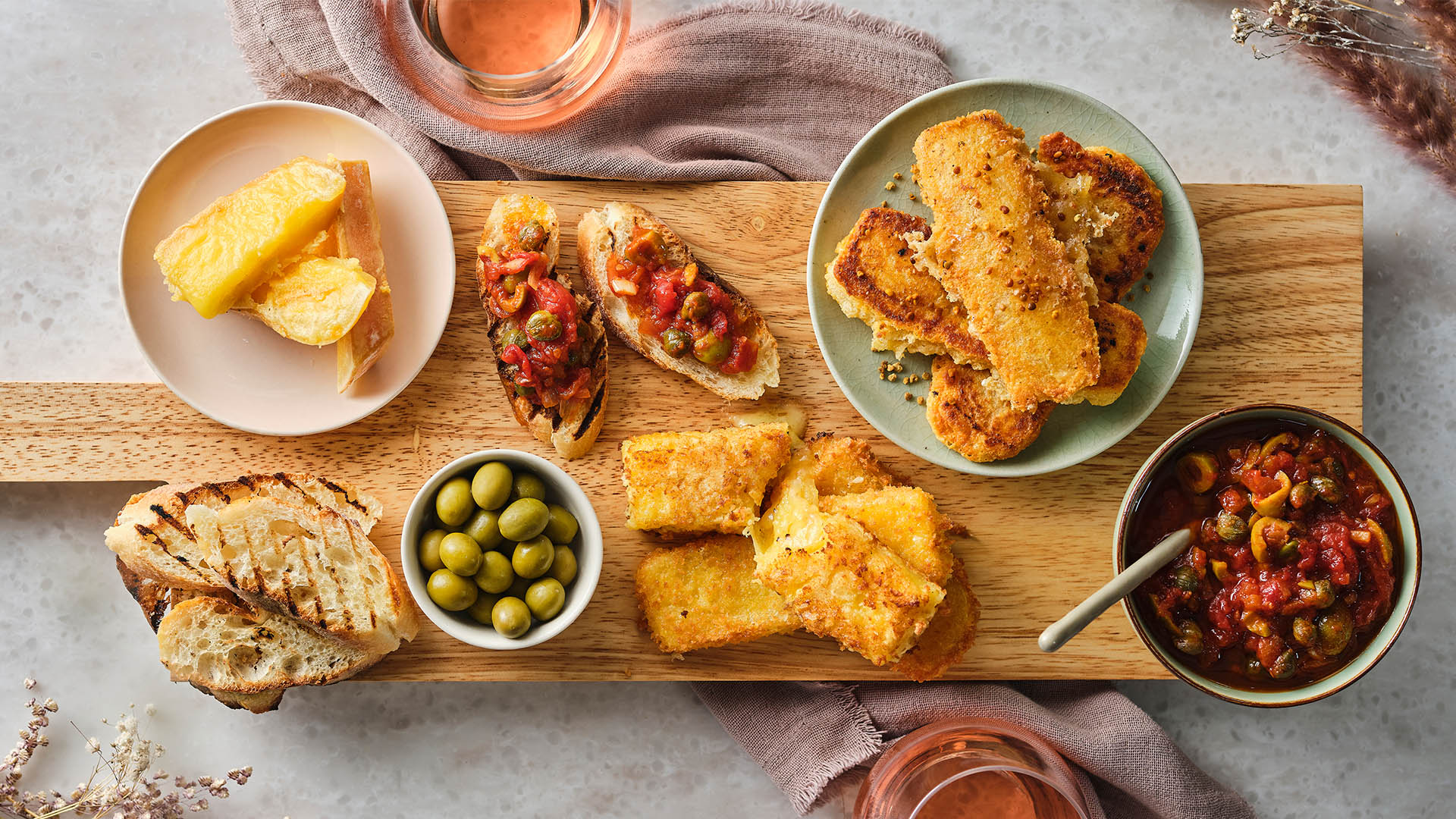 A cheeseboard features pan-fried and breaded and deep fried Ontario Artisan cheese on a cheeseboard surrounded by stewed tomato tapenade and garlic crostini.