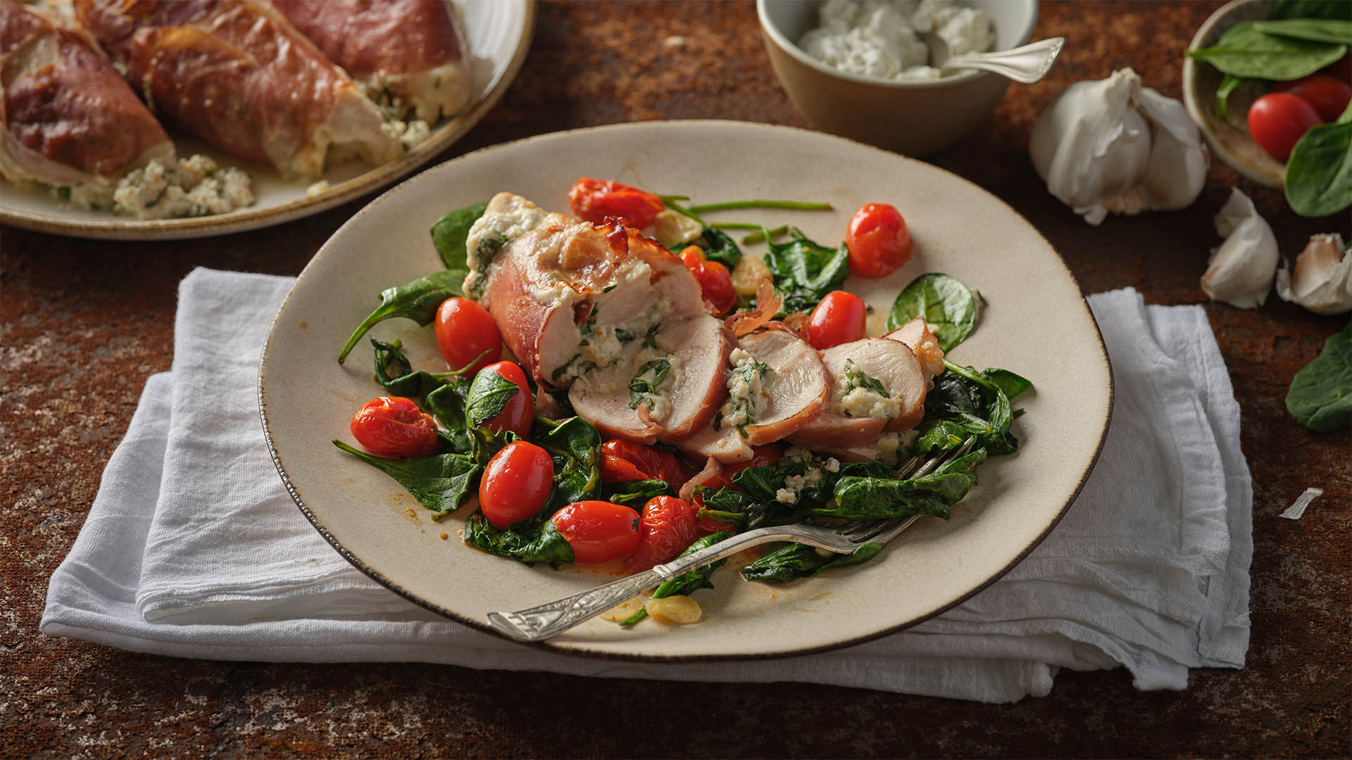 Quark stuffed chicken surrounded by cherry tomatoes and green vegetable on a white plate on top of a white napkin surrounded by quark cheese and cooked chicken in the background.