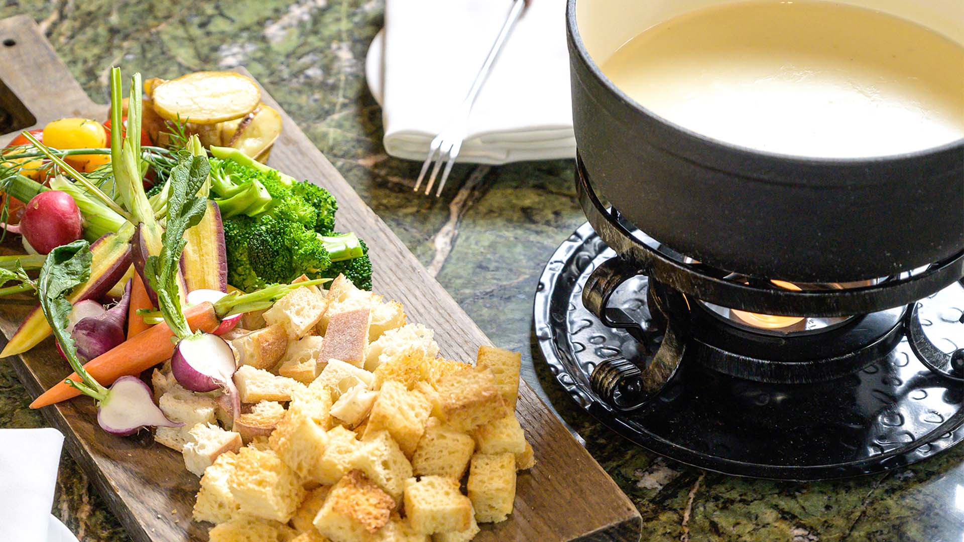 Cheese fondue in a black fondue pot, with fresh baked croutons and fresh garden vegetables for dipping on the side on a wooden cutting board.