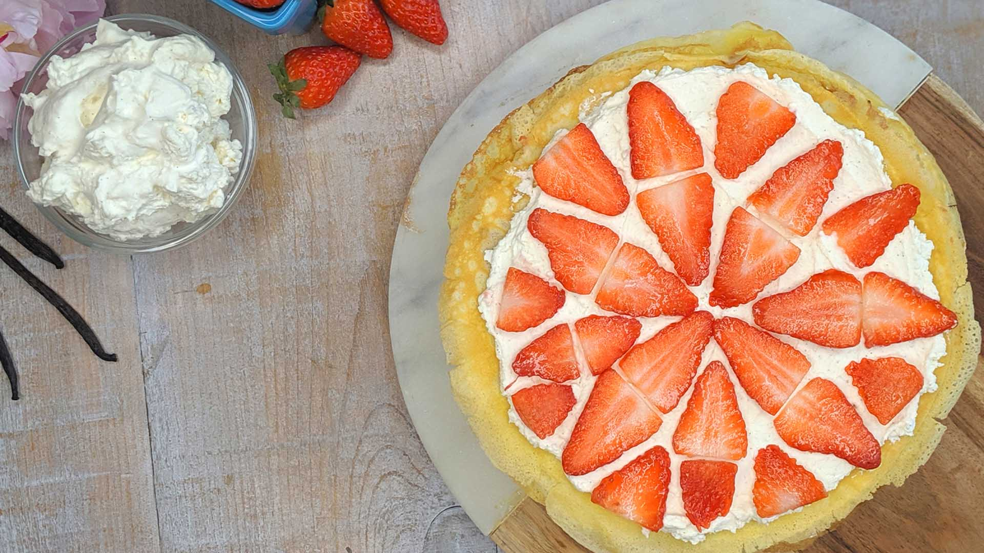 Overhead shot of round crepe cake topped with strawberry slices on wooden surface.