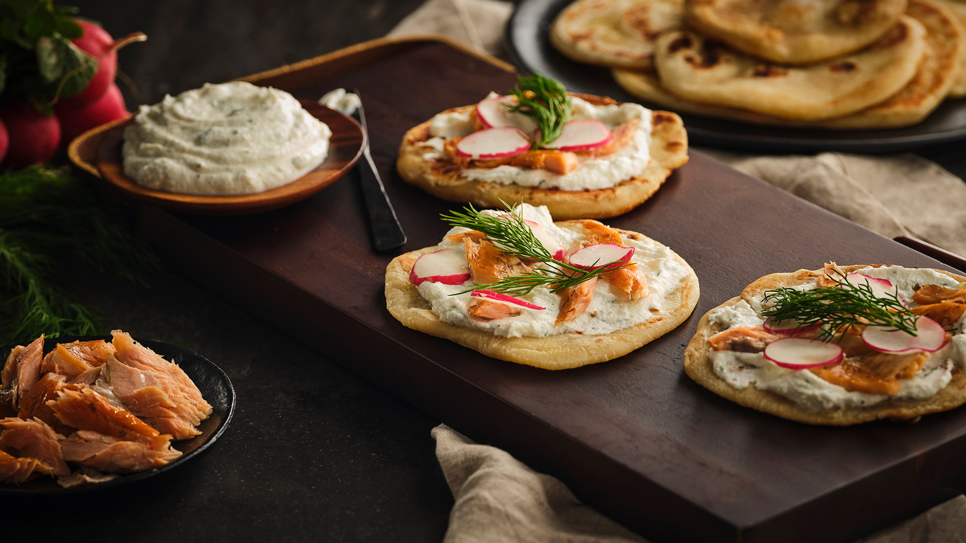 Flatbreads on wood board with radish, Labneh and garnish
