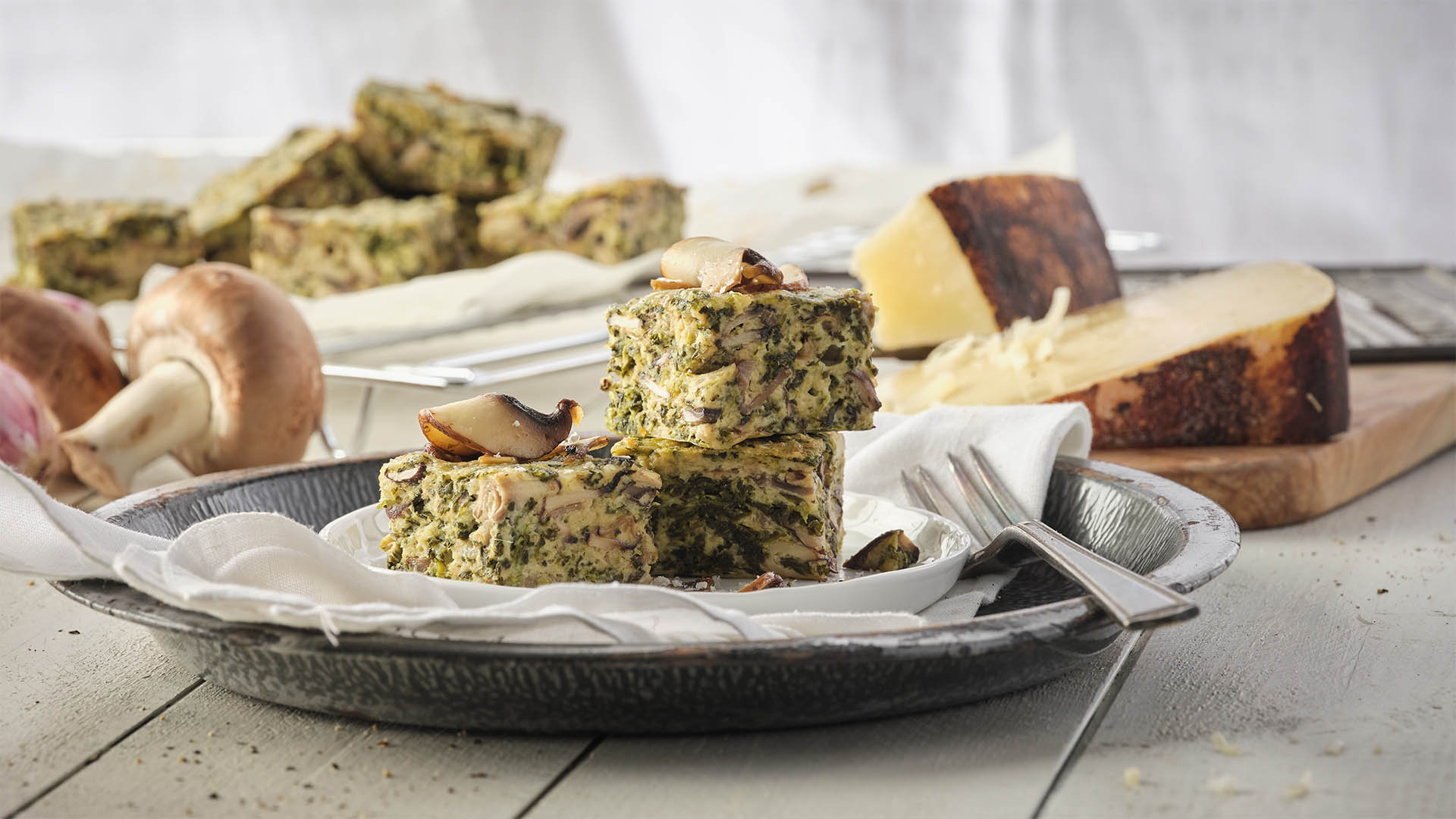 Spinach and Mushroom squares cut and placed onto a white serving plate, surrounded by cheese, mushrooms, and white linens on a grey rustic table. More squares in the background.