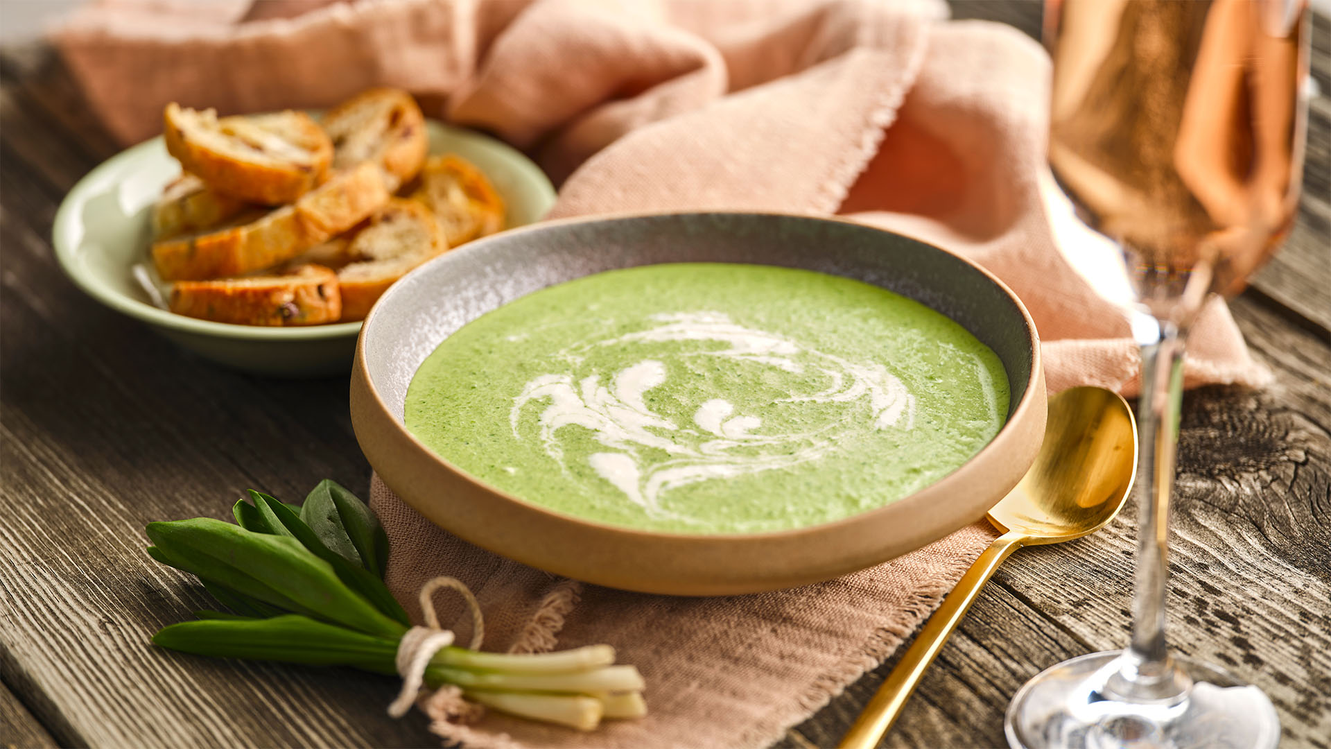 Side shot of Leek Spinach Veloute in a brown round bowl next to a bundle of leeks.